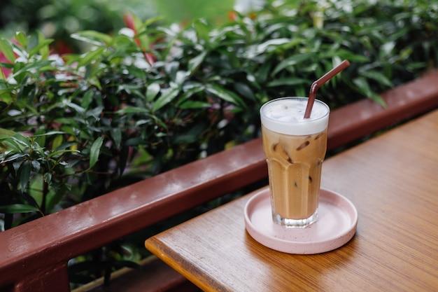 Iced latte in glas op een roze stand op houten tafel in zomerterras groene struiken