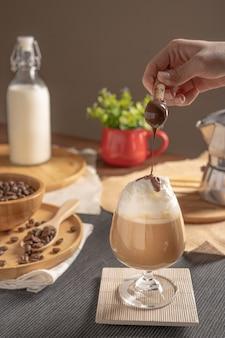 Iced latte koffie geserveerd met slagroom topping en chocoladesiroop in glas wijn plaats op houten tafel