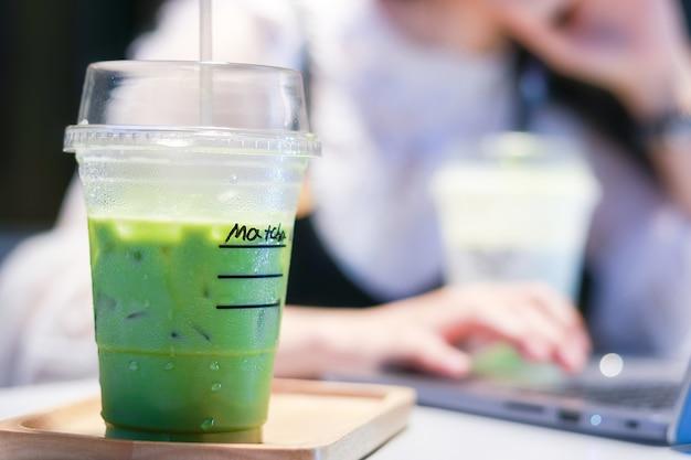 Iced matcha groene thee latte op tafel met vrouwen die in de winkel werken.
