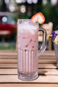 Iced strawberry milk geserveerd met plakjes aardbei.