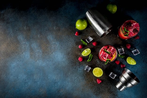 Iced zomer drankje cocktail, frambozen- en limoenlimonade met verse munt en limoen, donkerblauwe roestige tafel