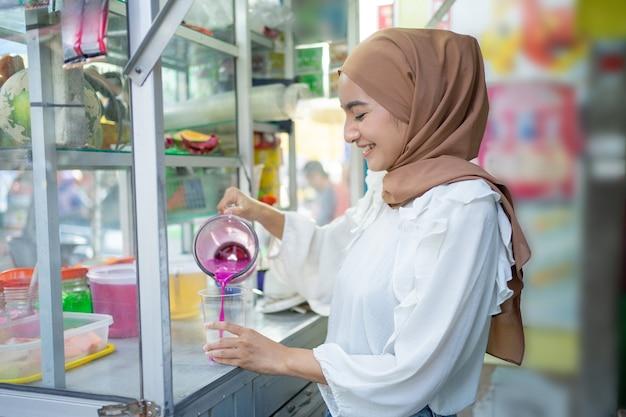Iceseller hijab meisje houdt een blender vast terwijl ze vruchtensap in een plastic beker giet