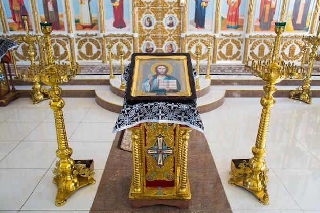 Icoon van jezus christus de almachtige op een vergulde standaard naast kandelaars