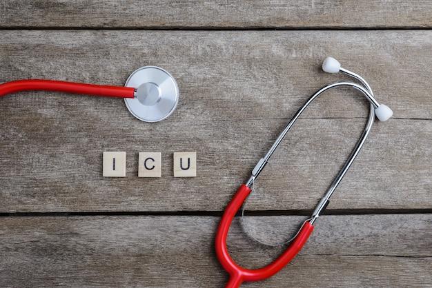 Icu-tekstwoord met houtsneden en rood hart, stethoscoop op houten lijst wordt gemaakt die