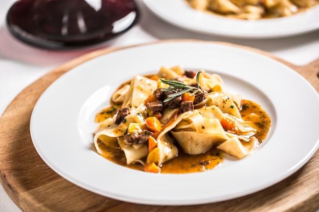 Idalian pasta pappardelle met rundvlees ragu op witte plaat en rode wijn.