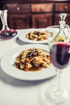 Idalian pasta pappardelle met rundvleesragout op witte plaat en rode wijn.