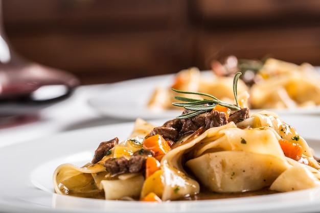 Idalian pasta pappardelle met rundvleesragout op witte plaat.