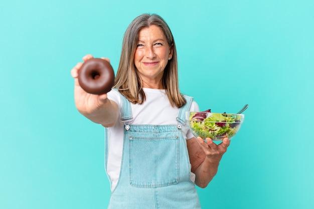 Iddle leeftijd mooie vrouw met een donut en een salade. dieet concept