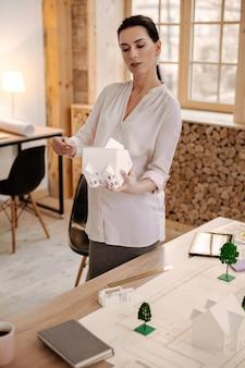 Ideaal huis. professioneel gerichte zwangere ontwerper die het huismodel schat terwijl hij het vasthoudt en op kantoor blijft