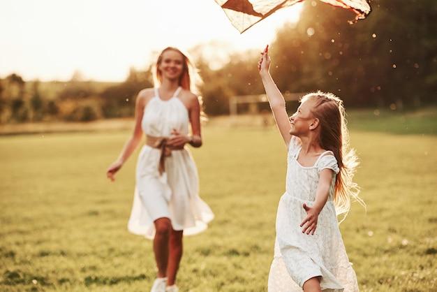 Ideaal warm weer. moeder en dochter hebben plezier met vlieger in het veld. prachtige natuur.