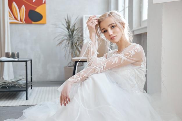 Ideale bruid zittend op de vloer, portret van een meisje in een lange witte jurk