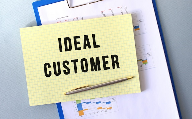 Ideale klant tekst geschreven op kladblok met potlood. kladblok op een map met diagrammen. financieel concept.