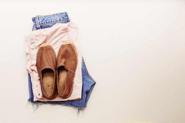 Ideale kleding voor zomerse outfits: een shirt, jeans, schoenen. uitzicht van boven.