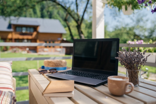 Ideale plek om in de zomer te werken. laptop, kladblok en kopje koffie staan op een houten tafel. bedrijfsconcept foto