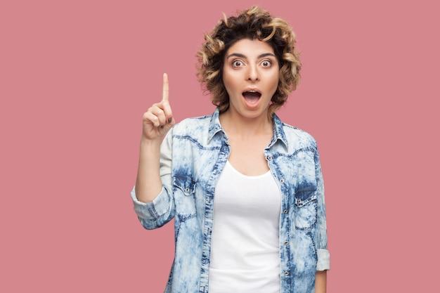 Idee. portret van een verraste jonge vrouw met krullend kapsel in een casual stijl die staat en naar de camera kijkt met een verbaasd gezicht en een ideevingergebaar. indoor studio opname, geïsoleerd op roze achtergrond.