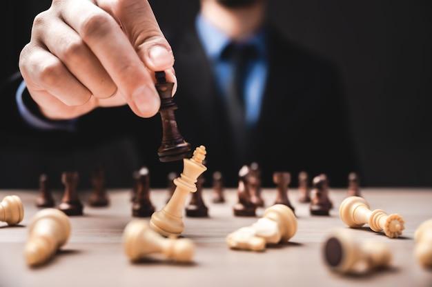 Idee van winnaar, zakelijk leiderschap en succesvol concept met schaakstukken en zakenmanhand