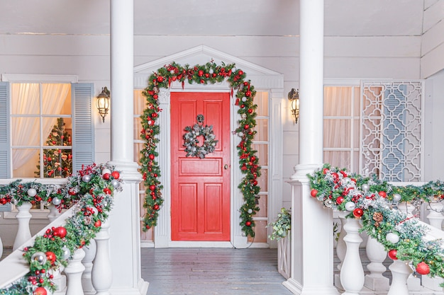 Idee voor de decoratie van de veranda van kerstmis huisingang met rode deur die voor vakantie wordt verfraaid