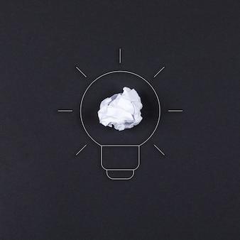 Ideeconcept met lamp, verpletterd document op zwarte hoogste mening als achtergrond. horizontaal beeld