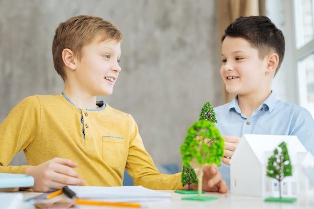 Ideeën delen. aangename, vrolijke pre-tienerjongens die aan tafel zitten en samen hun ecologieproject bespreken, ideeën uitwisselen over het creëren van een ecostad