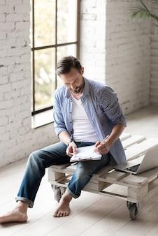 Ideeën noteren. aardige serieuze knappe man zit in de kamer en leunt over zijn aantekeningen terwijl hij iets schrijft met zijn potlood
