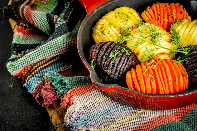 Ideeën van veganistisch eten, herfstrecepten van groenten. geroosterde hasselback-bieten, wortelen, aardappelen, met verse kruiden, in een koekenpan, op een zwarte stenen tafel,