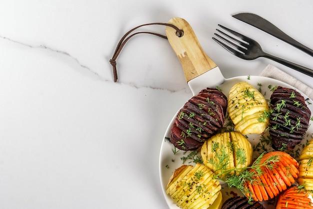 Ideeën van veganistisch eten, herfstrecepten van groenten. geroosterde hasselback-bieten, wortelen, aardappelen, met verse kruiden, op een bord, op een wit marmer, bovenaanzicht copyspace