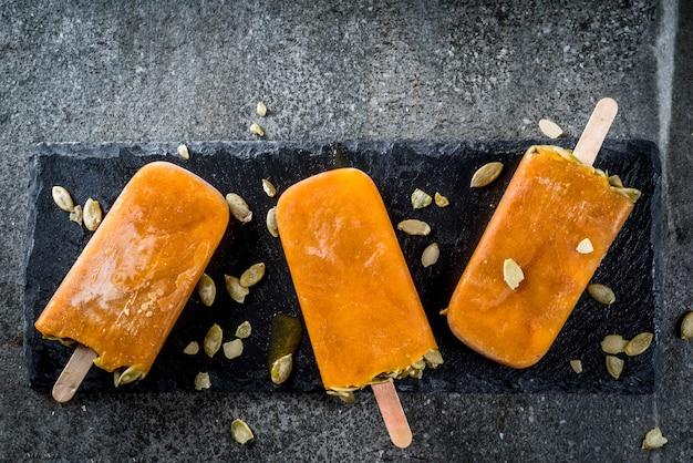 Ideeën voor herfstgerechten van pompoenen. traktaties voor een thanksgiving-feest, halloween. pompoenijsijslollys met zaden