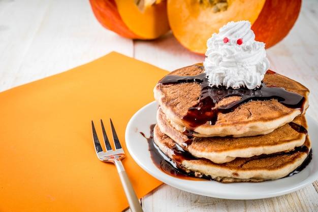 Ideeën voor het ontbijt van kinderen, traktaties voor thanksgiving en halloween. pannenkoeken met chocoladesaus en slagroom in de vorm van een geest. op een witte houten tafel,