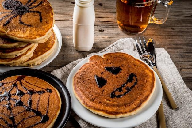 Ideeën voor het ontbijt zijn halloween, eten voor kinderen. pompoentaartpannenkoekjes versierd met chocoladesiroop in een traditionele stijl - spinnenweb, spin, jack lantaarn. op houten rustieke tafel, kopie ruimte