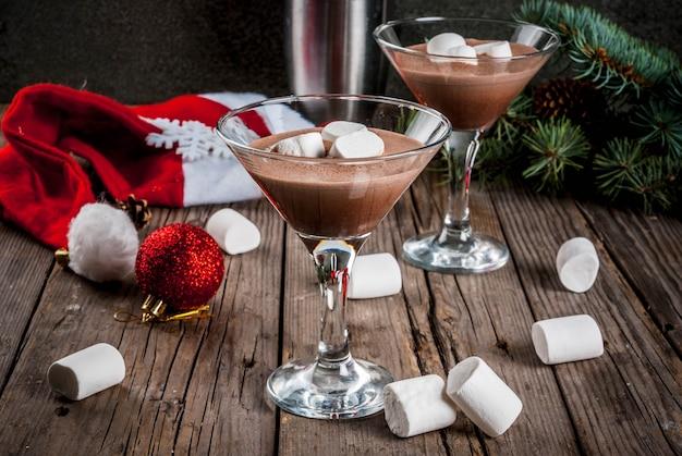 Ideeën voor kerstfeestdrankjes, zelfgemaakte hot chocolate martini-cocktails met marshmallow, op oude rustieke houten tafel met kerstversiering, kopie ruimte