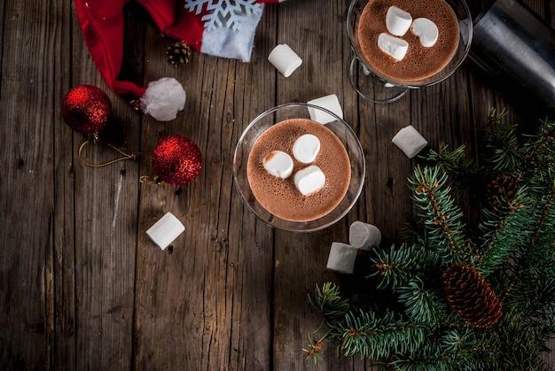 Ideeën voor kerstfeestjes drinken zelfgemaakte hot chocolate martini-cocktails met marshmallow op oude rustieke houten tafel met kerstversiering