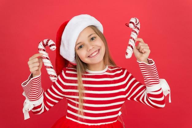 Ideeën voor kerstversiering. decoratie winkel. kerst decor. kerstvakantie. kind kerstman hoed houden kerst candy cane rode achtergrond. haar favoriete seizoen. winkelconcept. koop goederen.