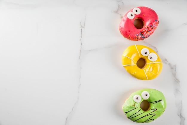 Ideeën voor kinderen traktaties op halloween. kleurrijke donuts in de vorm van monsters