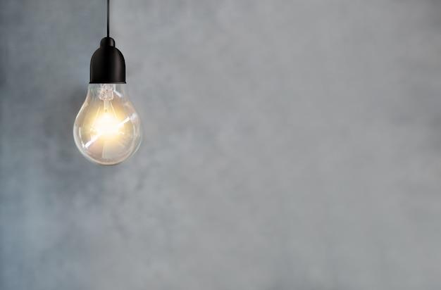 Ideeënergie en gloeilamp op de achtergrond van de cementmuur