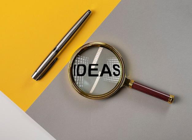Ideeënwoord op trendy gekleurde tafel met vergrootglas.