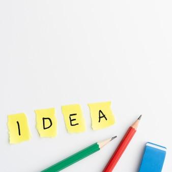 Ideetekst op gescheurd geel stukkendocument met potloden en gom over witte achtergrond