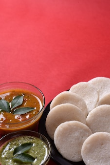 Idli met sambar en kokoschutney op rood oppervlak, indian dish: zuid-indiaas favoriete eten rava idli of griesmeel werkeloos of rava werkeloos, geserveerd met sambar en groene chutney.
