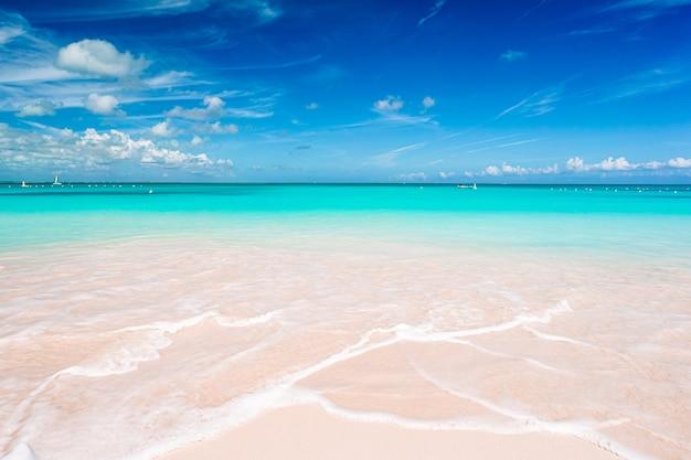 Idyllisch tropisch strand in het caribisch gebied met wit zand, turkoois oceaanwater en blauwe hemel