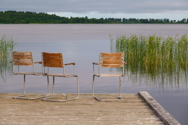 Idyllisch uitzicht op de houten pier in het meer met stoelen voor onderhandelingen