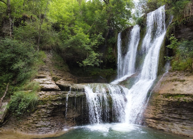 Idyllische regenwoudwaterval, stroom die in het weelderige groene bos stroomt.