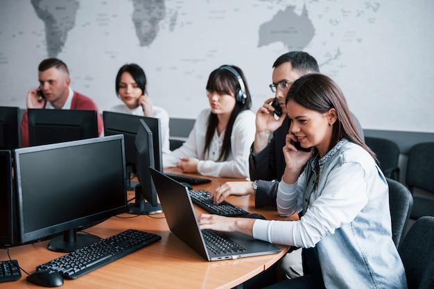 Iedereen doet zijn werk. jonge mensen die in het callcenter werken. er komen nieuwe deals aan