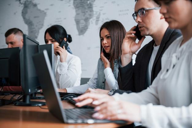 Iedereen praat tegelijkertijd. jonge mensen die in het callcenter werken. er komen nieuwe deals aan