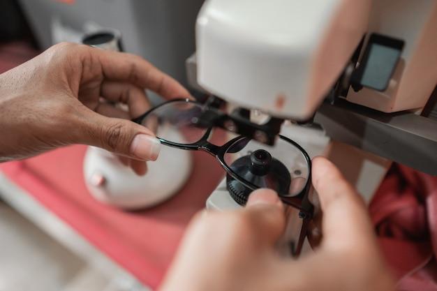 Iemand controleert de bril van een patiënt met een lenzenvloeistofchecker in een oogkliniek