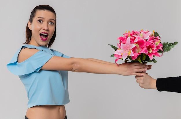 Iemand die een boeket bloemen geeft aan een opgewonden mooie jonge vrouw die op zoek is