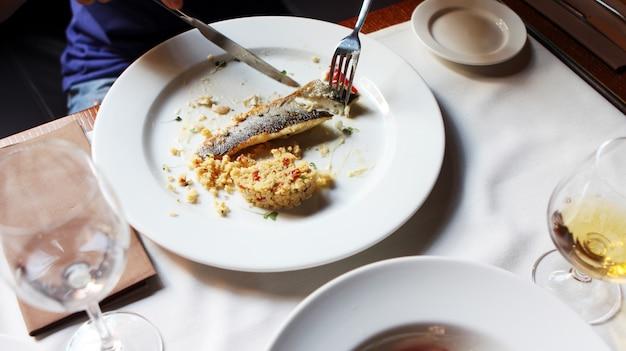 Iemand die een vis eet in een restaurant