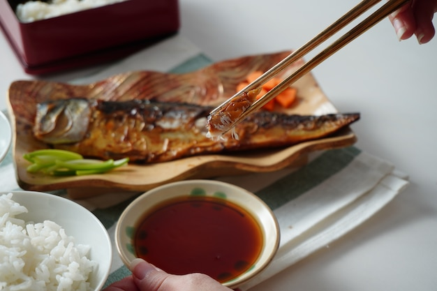 Iemand die eetstokjes gebruikt en een stuk gegrilde saba of makreel probeert te plukken geserveerd met gekookte rijst en misosoep op witte en groen gestreepte placemat op witte tafel