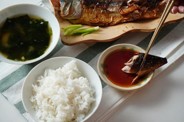 Iemand die eetstokjes gebruikt en een stuk gegrilde saba of makreelvis probeert te plukken en op zoete saus plakt, geserveerd met gekookte rijst en misosoep op witte en groen gestreepte placemat op witte tafel