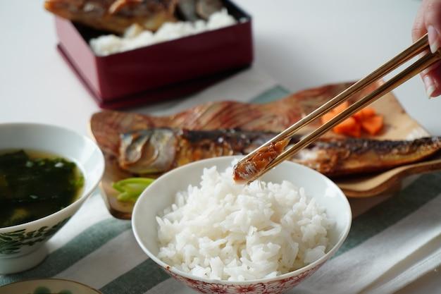 Iemand die eetstokjes gebruikt om een stuk gegrilde saba of makreelvis te kiezen, geserveerd met gekookte rijst en miso-soep op wit en groen gestreepte placemat op witte tafel