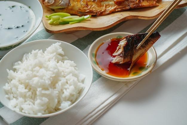Iemand die eetstokjes gebruikt om een stuk gegrilde saba of makreelvis te plukken en op zoete saus te plakken, geserveerd met gekookte rijst en miso-soep op wit en groen gestreepte placemat op witte tafel