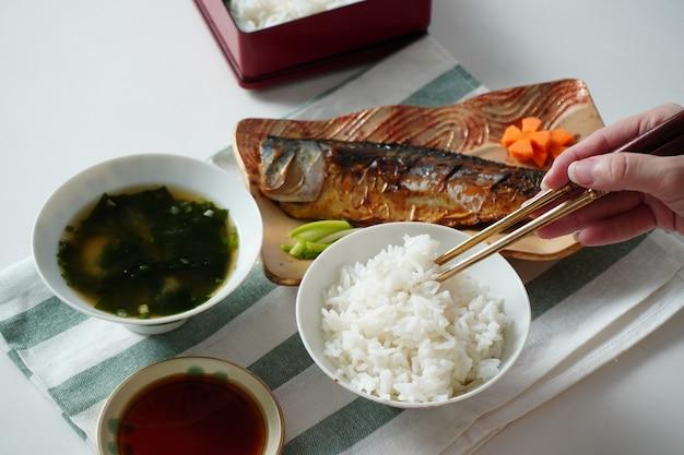 Iemand die eetstokjes gebruikt om gekookte rijst te plukken, geserveerd met een gegrilde saba